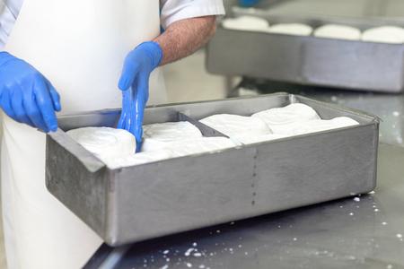 Mujer trabajadora preparando masa cruda de queso en moldes Foto de archivo