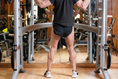 sport, bodybuilding, lifestyle and people concept - young man with barbell doing squats in gym.