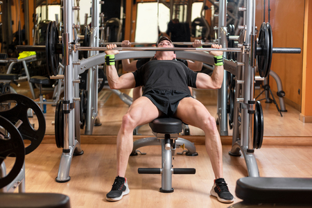 sport, bodybuilding, lifestyle and people concept - young man with barbell flexing muscles and making bench press in gym Stockfoto