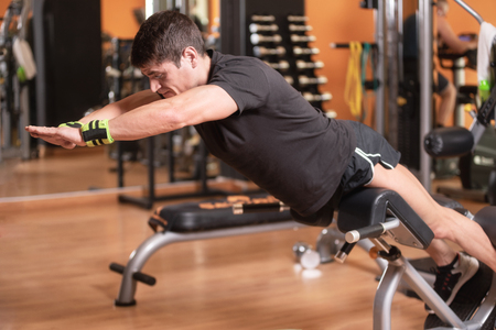 Lower back exercises for strengthening the muscles for spine health. Fitness man doing exercise workout with arms raised on gym bench. Bodyweight training.