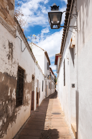 Old typical narrow street in the jewish quarter of Cordoba with old buildings with white walls. Standard-Bild