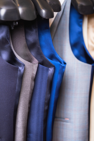 Stylish mens vest close up. Male svest hanging in a row. Mens Clothing, shopping in boutiques. vest and suits in a male luxury store.
