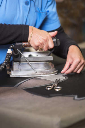 Semstress ironing the fabric. seamstress irons fabirc in a sewing workshop. Imagens