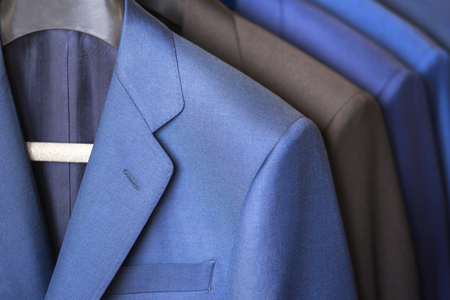 close up luxurious style gentlemen suit row, hanging in a closet. Imagens