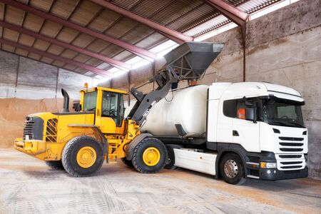 Tractor loading grain into truck at at grain processing plant warehouse, during harvesting time. Reklamní fotografie