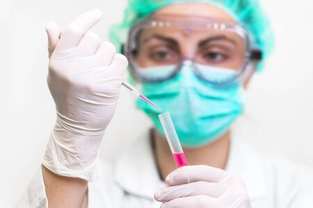 Young attractive concentrated female scientist in protective eyeglasses, mask and gloves dropping a red liquid substance into the test tube with a pipette in the laboratory.