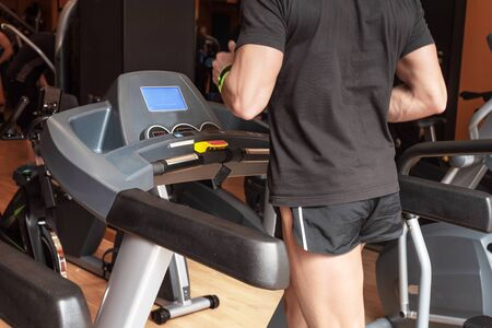 Man running in a modern gym on a treadmill, concept for exercising, fitness and healthy lifestyle. Stock Photo