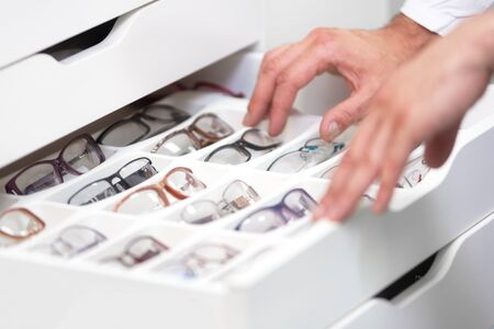 ophthalmologist hands close up, choosing glasses from a drawer in the optical store. Banque d'images
