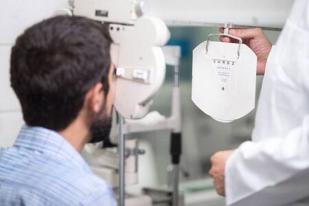 Der Augenarzt des männlichen Arztes überprüft die Sehkraft eines gutaussehenden jungen Mannes in einer modernen Klinik. Arzt und Patient in der Augenklinik.
