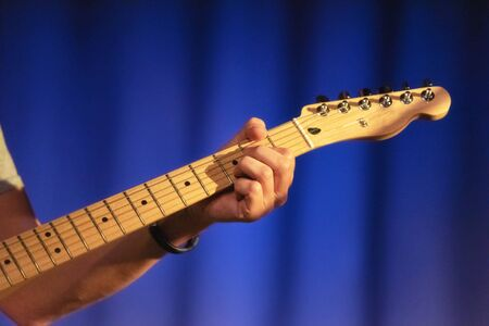 Male hands playing on electric guitar, close up.