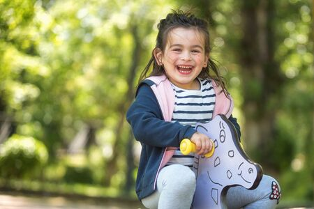 Cute girl enjoying on playground in the park in summertime.