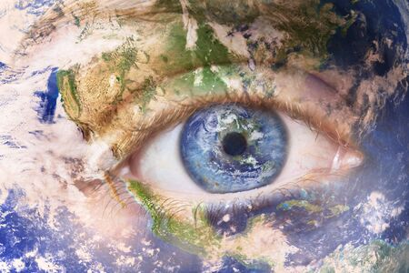 Earth awakening concept, save the planet. Close up image of woman face with earth painted. Creative composite of macro Eye with Earth as Iris. Elements of this image furnished by NASA.
