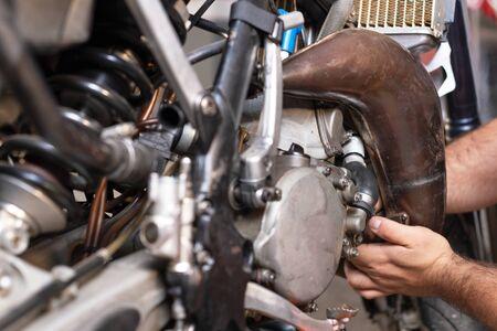 Motorbike mechanic repairing an exhaust pipe system at garage. Stockfoto