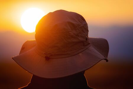 Back view of a man with explorer hat watching scenic sunset. Concept for travel exploration and discovery. Banco de Imagens