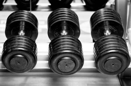 Different sizes and weights of dumbbell free weights at a gym in black and white.
