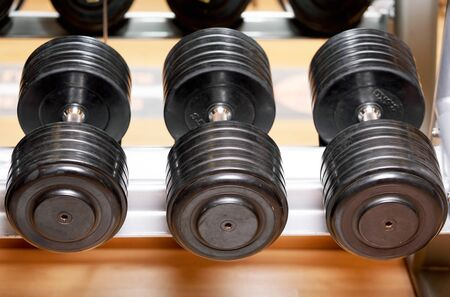 Different sizes and weights of dumbbell free weights at a gym.