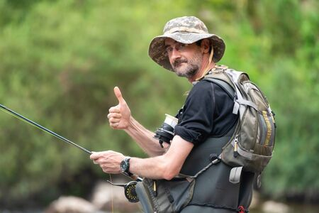 Happy fisherman with a beard on the river bank with a fishing rod in his hands, showing thumbs up. Summer holidays.