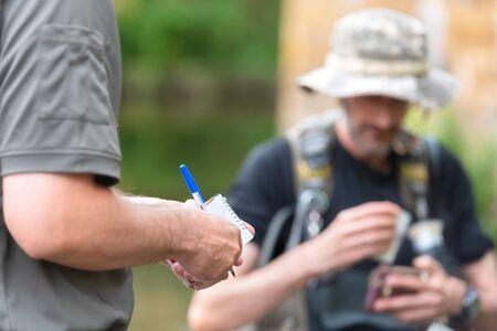Polizist oder Ranger, der die Fischerlizenz im Fluss überprüft. Fischereiinspektion. Gesetz.