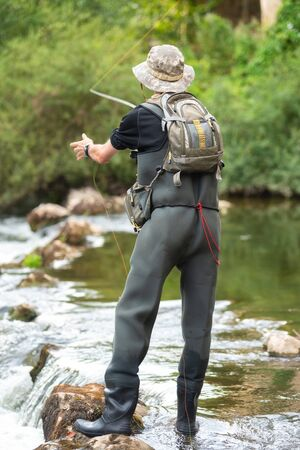 Fisherman fishing on the River, holding Fishing Rod.