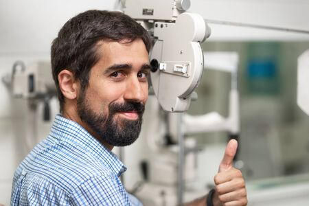 Patient in modern ophthalmology clinic checking the eye vision, showing thumb up.