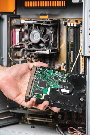 Closeup image of technician man hand changing the hard drive of pc computer . Maintenance and repair computer hardware service concept.