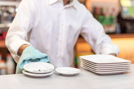Waiter drying dishes in the restaurant. Reklamní fotografie