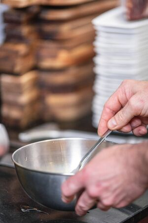 Chef hands beating eggs in a bowl.