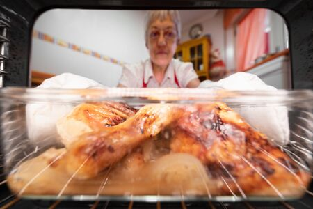 Senior woman taking roasted chicken from the oven, viewed from the interior.
