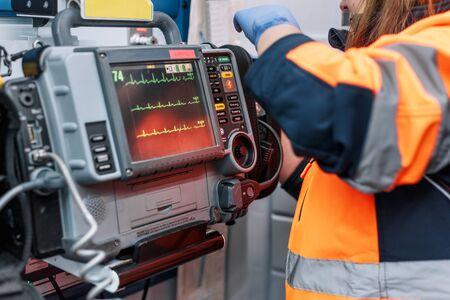 Medical urgency in the ambulance. Emergency doctor using defibrillator.