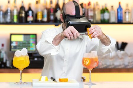 Barman apprentice preparing cocktail with virtual reality teacher. Apprentice learning how to prepare cocktail with virtual reality glasses.