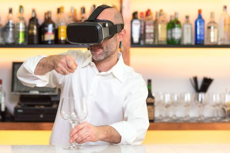 Barman apprentice training serving cocktail with virtual reality teacher. Apprentice learning how to prepare cocktail with virtual reality glasses. 写真素材