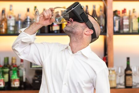 Barman apprentice training serving cocktail with virtual reality teacher. Apprentice learning how to prepare cocktail with virtual reality glasses .