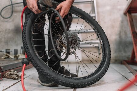 Mechanic repairing a bicycle tire flat in a small workshop . Reklamní fotografie