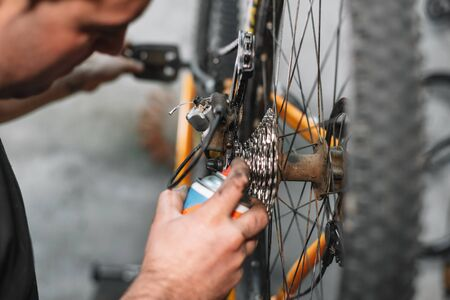 Mechanic man Hands, Spraying Oil To A Bike Chain. Bicycle maintenance .