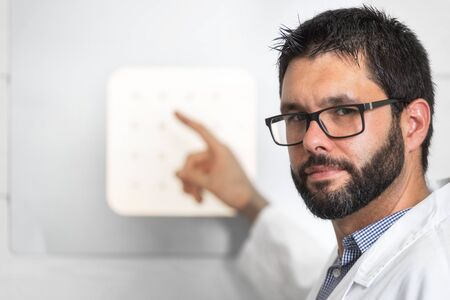 Doctor Optician With Letter Chart Conducting An Eye Test Check. Stockfoto