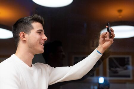 Portrait of Happy young man taking selfie at the coffee shop.