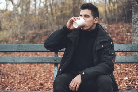 Young man sitted in a bench holding disposable coffee cup in the park in autumn season. 写真素材
