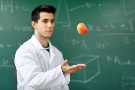 Lächelnder Student mit weißem Mantel, der einen Apfel hochwirft, auf grüner Tafel mit Gleichungshintergrund. Standard-Bild