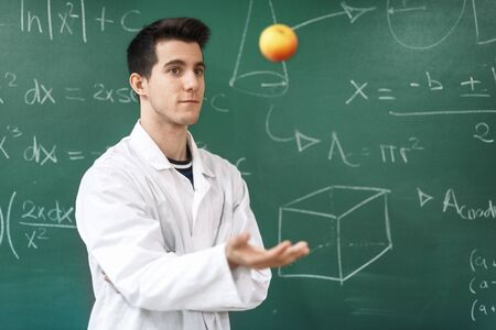 Smiling student with white coat throwing an apple up, on green chalkboard with equations background.