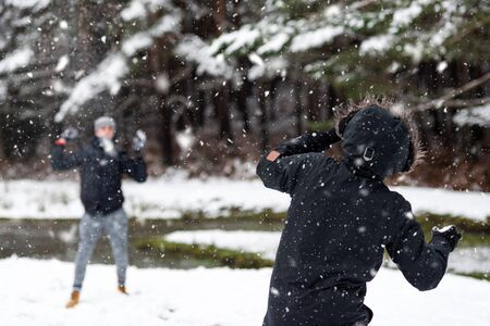 Young Happy friends enjoying throwing Snow balls, Having Fun in a Snowy Mountain. Stock Photo