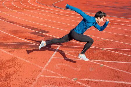 Corridore che inizia il suo sprint sulla pista di atletica in uno stadio. Archivio Fotografico