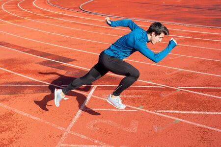 Runner starting his sprint on running track in a stadium. Фото со стока
