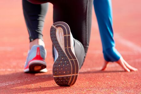 Back view of an athlete getting ready for the race on a running track. Focus on shoe of an athlete about to start a race in stadium. Фото со стока