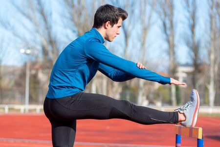 Young athlete stretching on a running track. Фото со стока