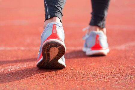 close up view of an athlete getting ready for the race on a running track . Focus, on shoe of an athlete about to start a race in stadium.