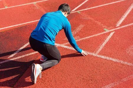 Man athlete on the starting line of a running track at the stadium.
