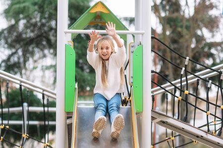 Happy little girl having fun on slide in park.
