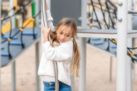 Pretty, little girl playing on children playground, ready to slide by pole. Фото со стока
