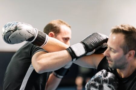 young man fighter, training kick boxing with his trainer, fighting in the ring. Фото со стока