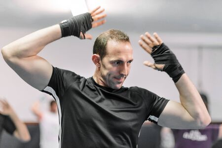 Fitness man warming up in gym. Preparing kick boxing combat. Фото со стока